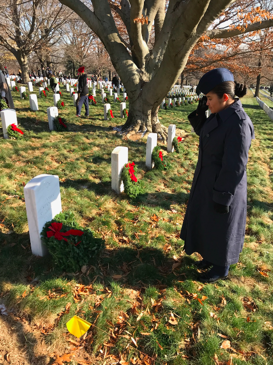 AF-JROTC Cadet salutes a grave after laying a wreath through the Wreaths Across America initiative.