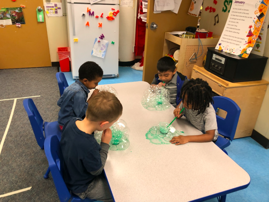 Photo of preschool students blowing bubbles.