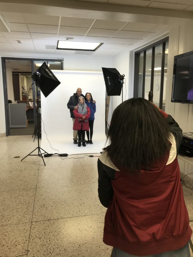 A family poses for a portrait taken by an ACC student