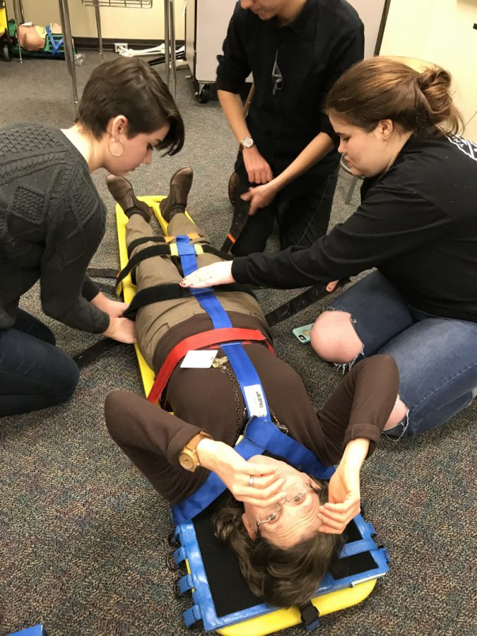 EMT students demonstrate how to use a backboard