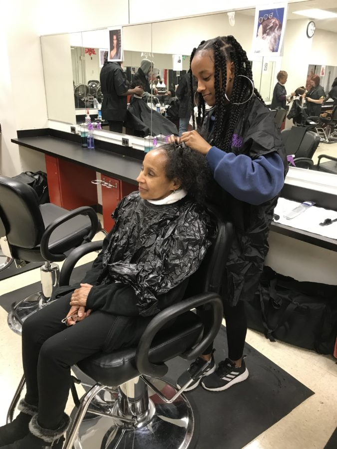 A cosmetology student styles a client's hair
