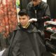 A barbering student styles a client's hair