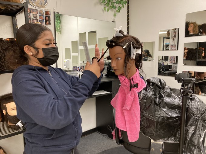 A Cosmetology student demonstrates hair curling technique.