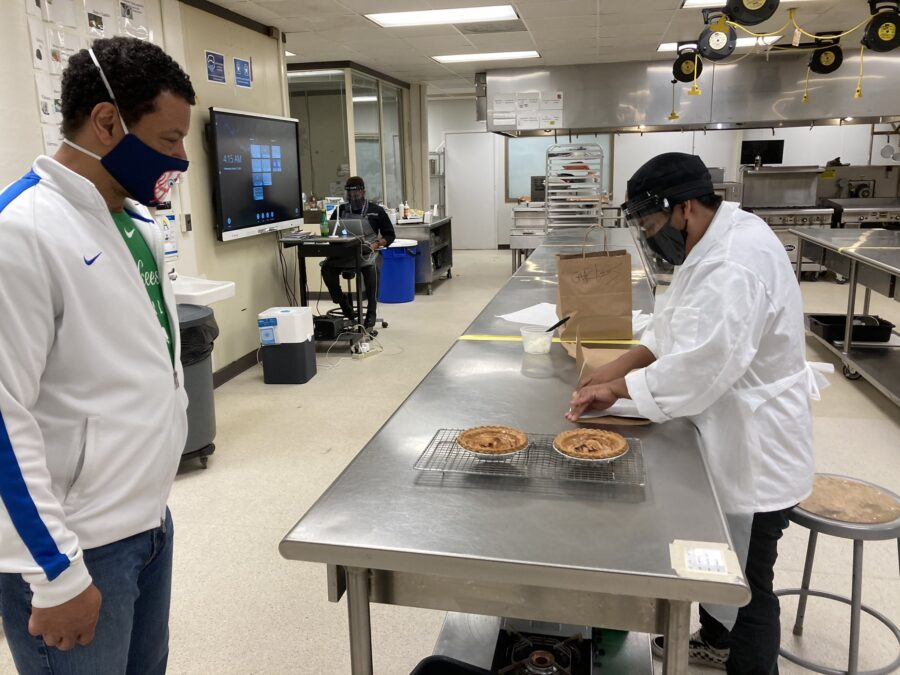 A Culinary Arts student boxes apple tarts while Mr. Byrd observes.