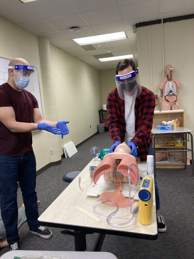 An EMT student practicing their skills on a dummy.