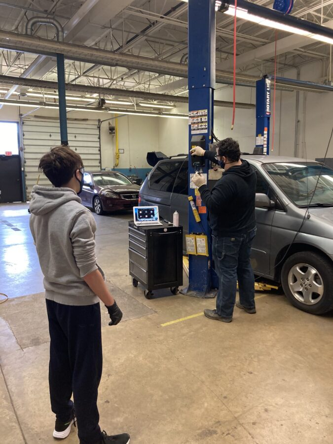 Auto Tech students observing Mr. Merker in the lab.
