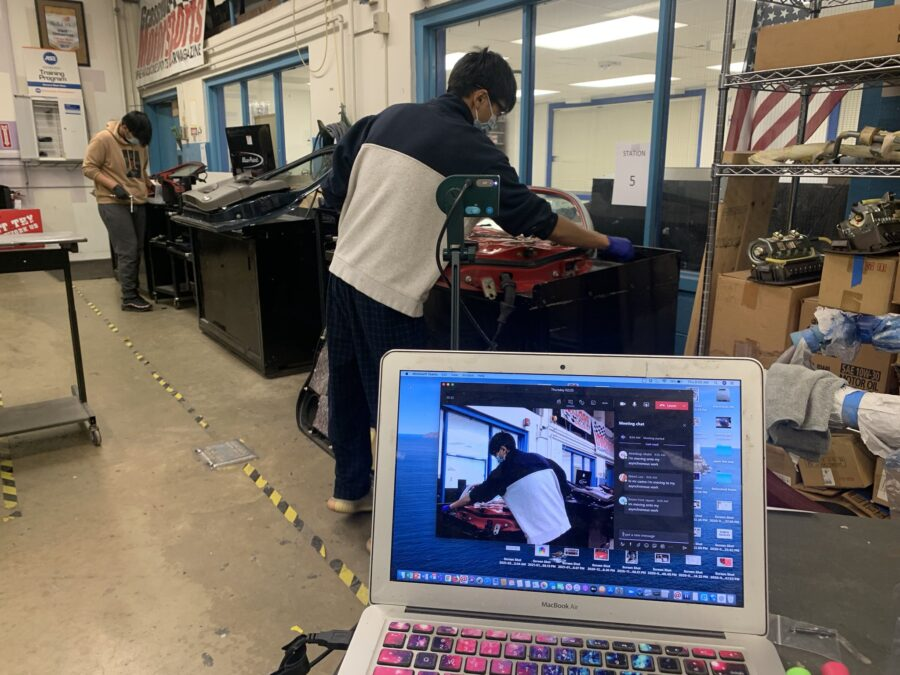 An Auto Collision Repair student showing virtual learners around the shop.
