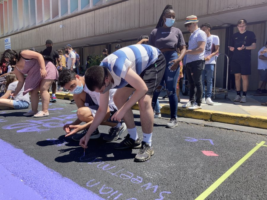 Student adds name to mural